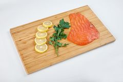 Fillet smoked trout with fresh herbs and lemon on a board. Seafood, isolated. Fillet trout with fresh herbs and lemon on a board. Seafood Royalty Free Stock Images
