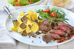 Fillet with truffles and pasta. Fried beef tenderloin with Italian pasta and slices of fresh black autumn truffles, served with a mixed side salad and baguette stock photos
