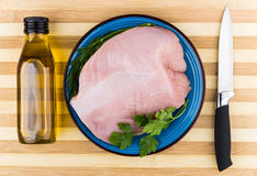 Fillet of Turkey breast with greens, bottle of oil Royalty Free Stock Photo