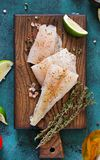 Fillet of white fish on a wooden board prepared for cooking Royalty Free Stock Photography