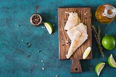 Fillet of white fish on a wooden board prepared for cooking. Stock Images