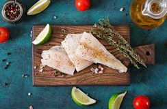 Fillet of white fish on a wooden board prepared for cooking. Stock Image