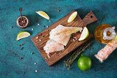 Fillet of white fish on a wooden board prepared for cooking. Royalty Free Stock Photos