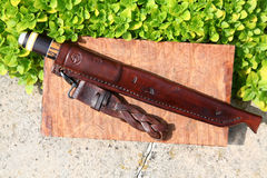 Filleting knife in decorated leather scabbard. A decorative filleting knife enclosed in a brown leather scabbard laying on a wall with a belt dangler attached Stock Photos
