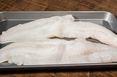 Fillets of cod fish on baking pan Royalty Free Stock Images