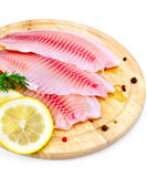 Fillets tilapia with lemon and dill on a board Royalty Free Stock Photography