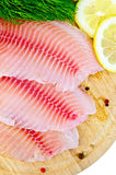 Fillets tilapia with lemon and dill on a round board stock image