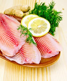 Fillets tilapia in pottery on the board Stock Photos