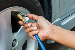 Filling air into a car tire.  royalty free stock photo