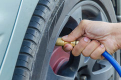 Filling air into a car tire Stock Images