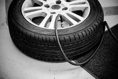 Filling air into car tire Royalty Free Stock Images