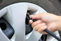 Filling air into a car tire Royalty Free Stock Photography