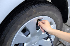 Filling air into a car tire Stock Photo