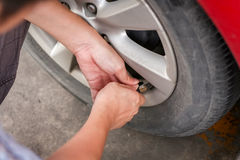 Filling air into a grungy car tire to increase pressure Royalty Free Stock Photography