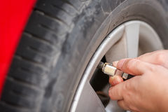 Filling air into a grungy car tire to increase pressure Stock Photos