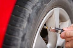 Filling air into a grungy car tire to increase pressure Stock Image