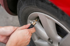 Filling air into a grungy car tire to increase pressure Royalty Free Stock Images