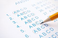 Filling answer sheet with pencil. Closeup view royalty free stock photo