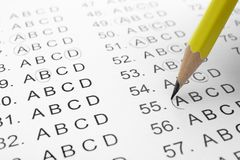 Filling answer sheet with pencil. Closeup view royalty free stock photography