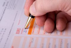 Filling a bank tranfer form. Close up on a mans hand filling an international bank transfer form Royalty Free Stock Image