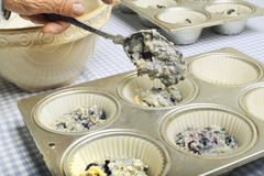 Filling batter in muffin tins. Royalty Free Stock Photo