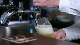 Filling of beer into a glass closeup stock footage