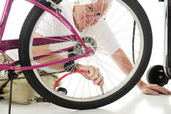 Filling the Bike Tire. A senior man looking the the viewer through the spokes of the girl's bike tire that he's filling with the hose for an air compressor.  On Stock Photography