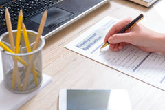 Filling in blank employment application form Stock Photography