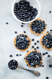Filling blueberry tart with fresh fruits Royalty Free Stock Images