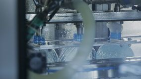 Filling bottles with drinking water on conveyor belt in workshop of company. stock footage