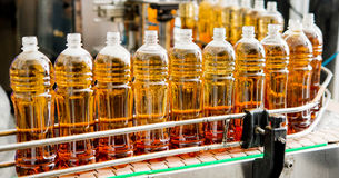 Filling bottles with juice. Filling bottles with sweet drink at a factory stock image
