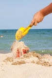 Filling bucket on beach Royalty Free Stock Images