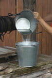 Filling bucket with water Stock Images
