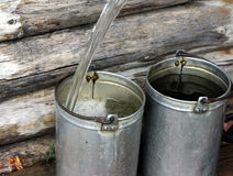 Filling bucket with water Royalty Free Stock Image