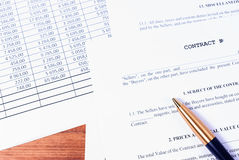 Filling business contract in terms of details of the parties. A contract with a lying pen and financial chart on the office Desk stock photos