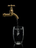Filling By Water Of A Glass From Brass Faucet Royalty Free Stock Photo
