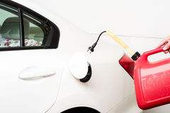 Filling a car with a gas can with electrical outlet. Red gas can with electrical plug royalty free stock photography