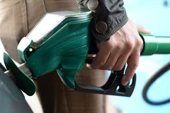 Filling the car with petrol. Man holding green delivery hose at petrol pump with nozzle directing fuel into tank and fingers shown pressing the delivery lever stock image