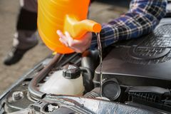 Filling the car water cooling system with fresh water Royalty Free Stock Photo