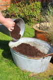 Filling container with compost. Royalty Free Stock Image