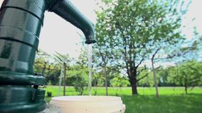 Filling the container with a water from the well pump stock video