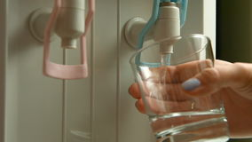 Filling cup at water cooler, water dispenser. Woman filling cup at water cooler, water dispenser stock video