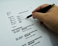 Man filling a resume with a pen royalty free stock photo