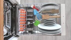 Filling dirty dishes in the dishwasher.Timelapse, 4K. A man puts dirty dishes in the dishwasher 4k