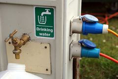 Filling a drinking water container at a campsite water and electricity supply point.  stock image