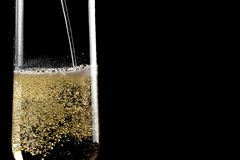 Filling a flute of champagne with golden bubbles Royalty Free Stock Images