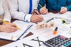 Filling 1040 form with advisor`s help, taxation company.  stock photo