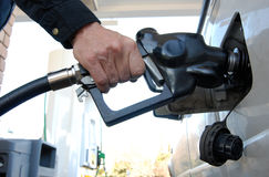 Filling gas tank. Close up of a customer's hand pumping fuel into car's gas tank stock photo