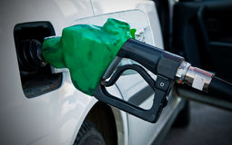 Filling the Gas Tank. Gasoline refueling pump with green handle in tank of car at gas station stock photography
