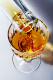 Filling of a glass by alcohol. Filling of a wine glass by a noble alcohol Stock Photo